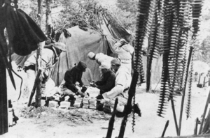 Historic photo from an army postal service outside of a tent.